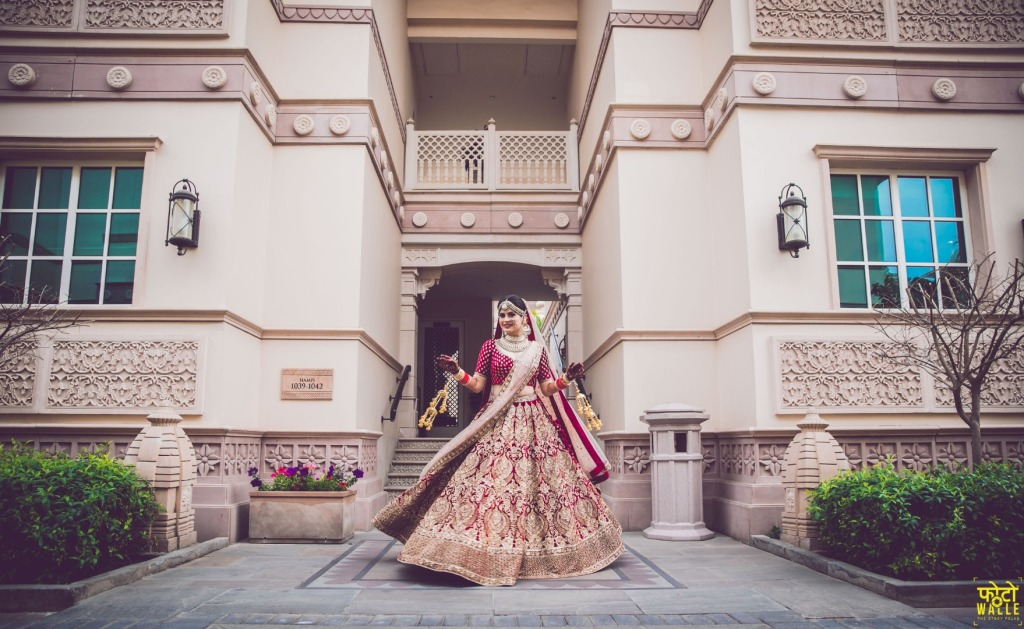 Twirling Bride Picture in Red Lehenga and Gold Kaleeras Solo Portrait