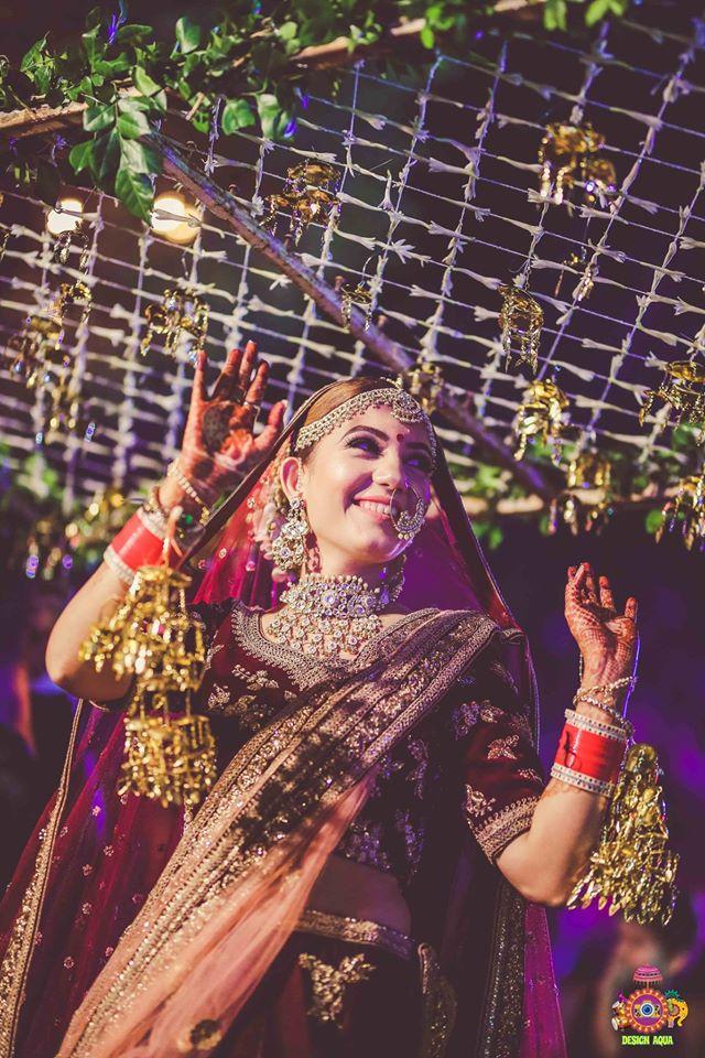 A Dancing Bride Coming Down The Aisle Under Phoolon Ki Chaadar with Hanging Kaleeras