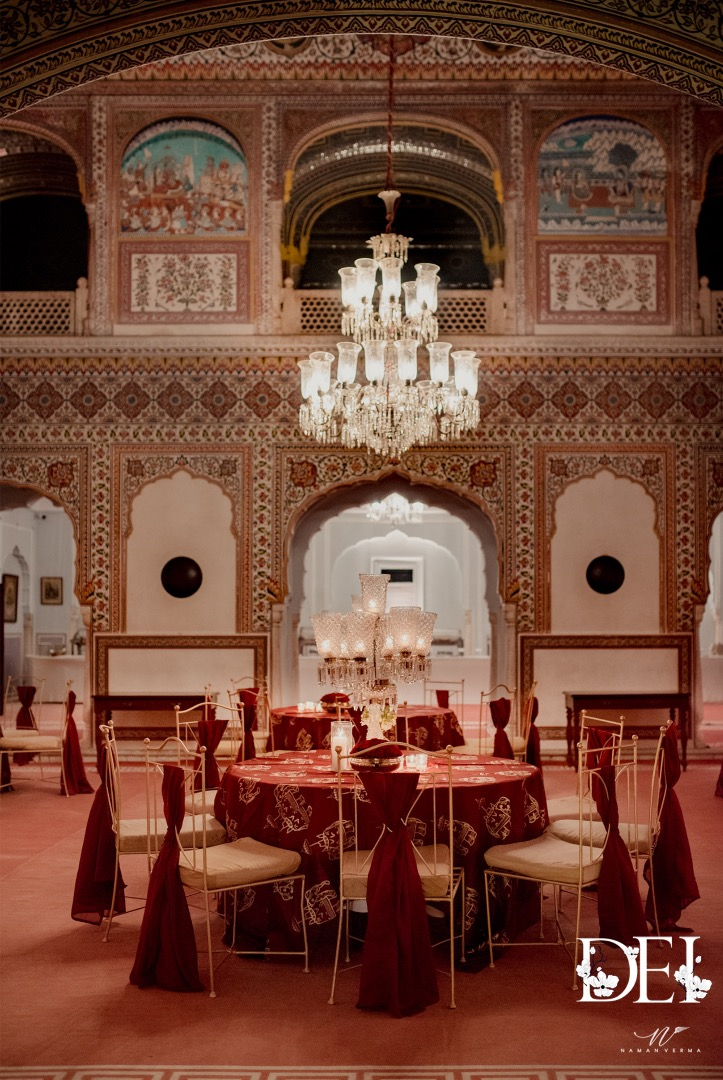 Royal Traditional Wedding Decor with Chandelier and Red Draped Table & Chairs
