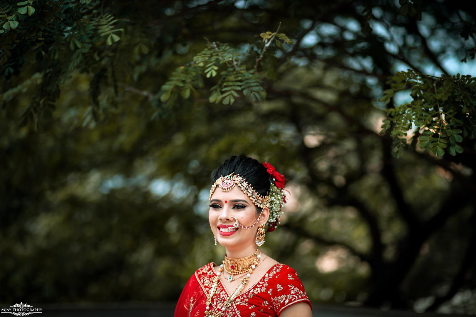 Smiling Bride Picture in Red Lehenga, Gold Jewellery & Floral Bun