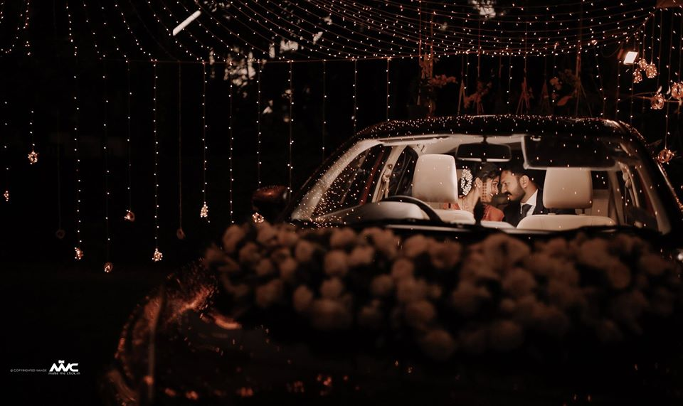 Bride & Groom Post Wedding Picture in Car with Floral Decoration and Fairy Lights